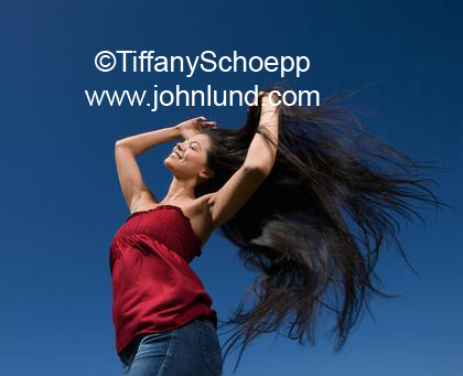 Photo of a Hispanic woman with her long black hair blowing in the wind. She is very happy and wearing a bright red silk blouse and blue jeans with a dark blue sky background.